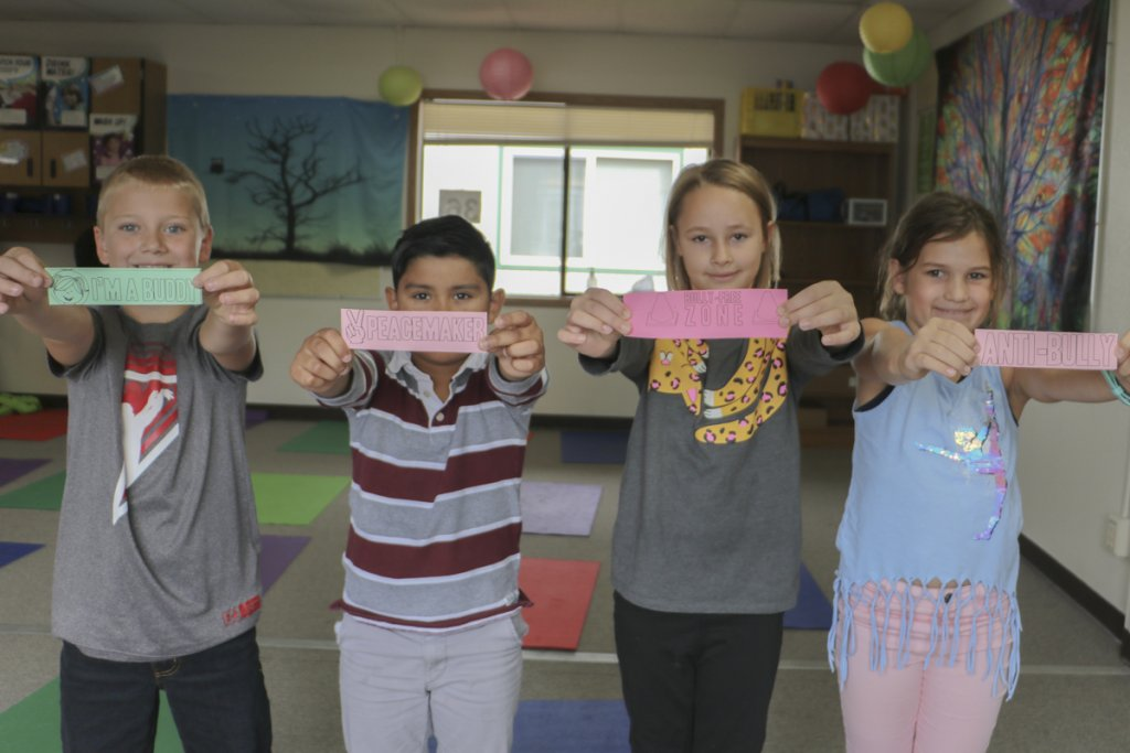 Captain Strong Primary School third graders hold up bookmarks with anti-bullying messages